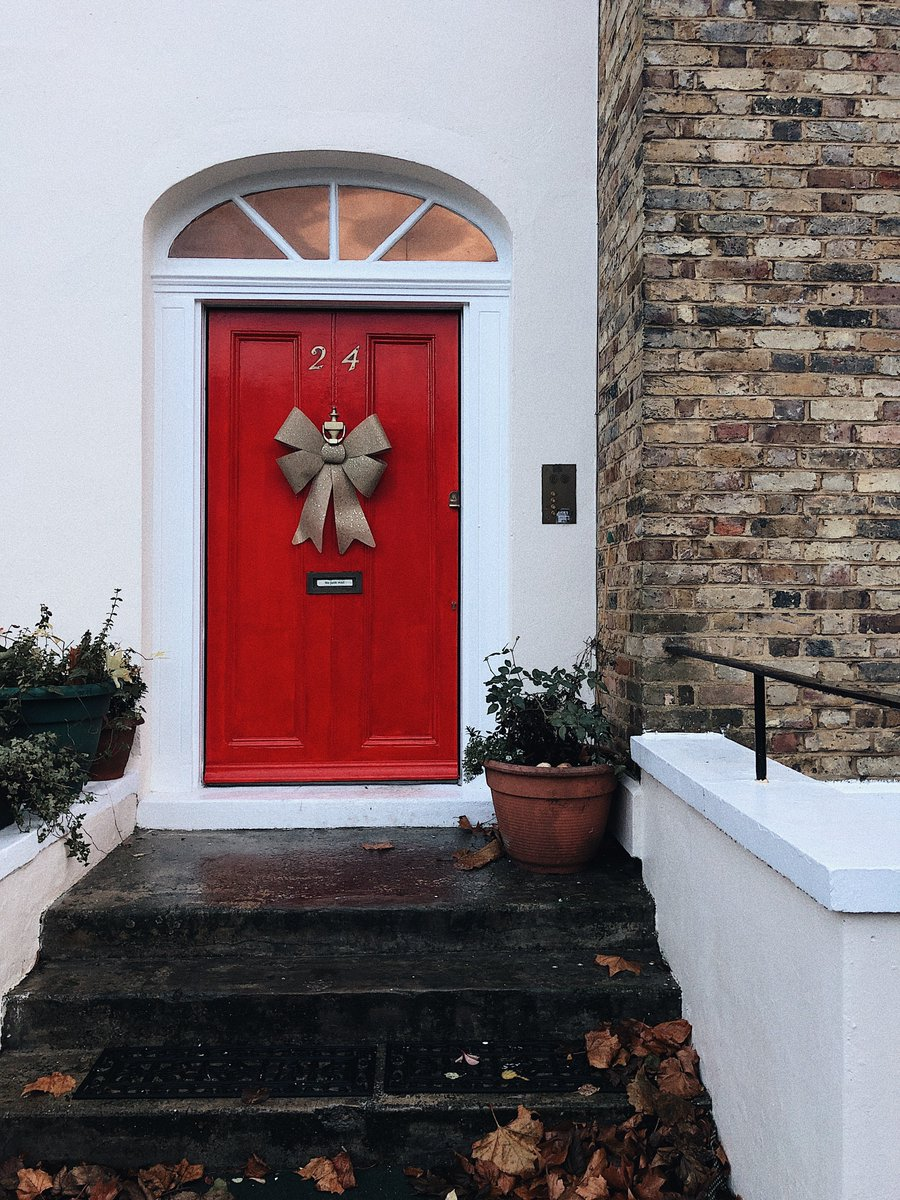 Steps leading up to a red wooden door with a bow on it.